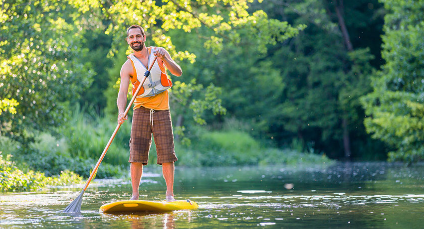 Stand up paddle along a stream in the woods