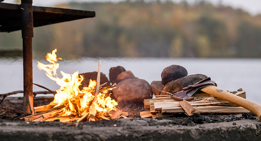 Fire burning in fireplace in the forest by a lake