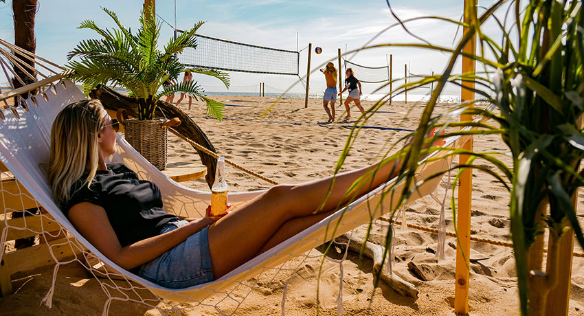 Girl lying in hammock on the beach