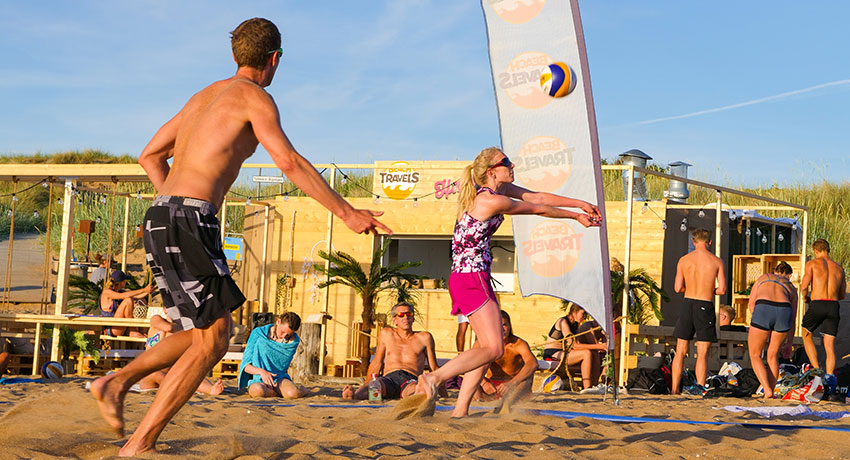 Two people playing beach volleyball on the beach