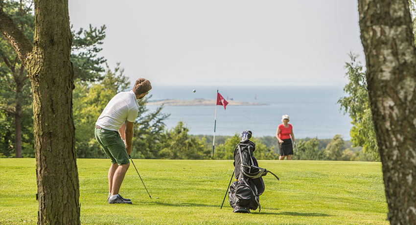 Person playing golf with view of the sea