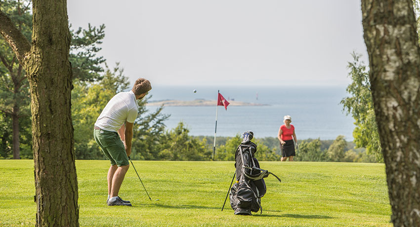Golfer at Ringenäs golf club with a view of the sea.